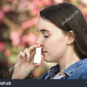 stock-photo-teenager-female-with-pollen-alergy-using-nose-inhaler-in-park-1070409131